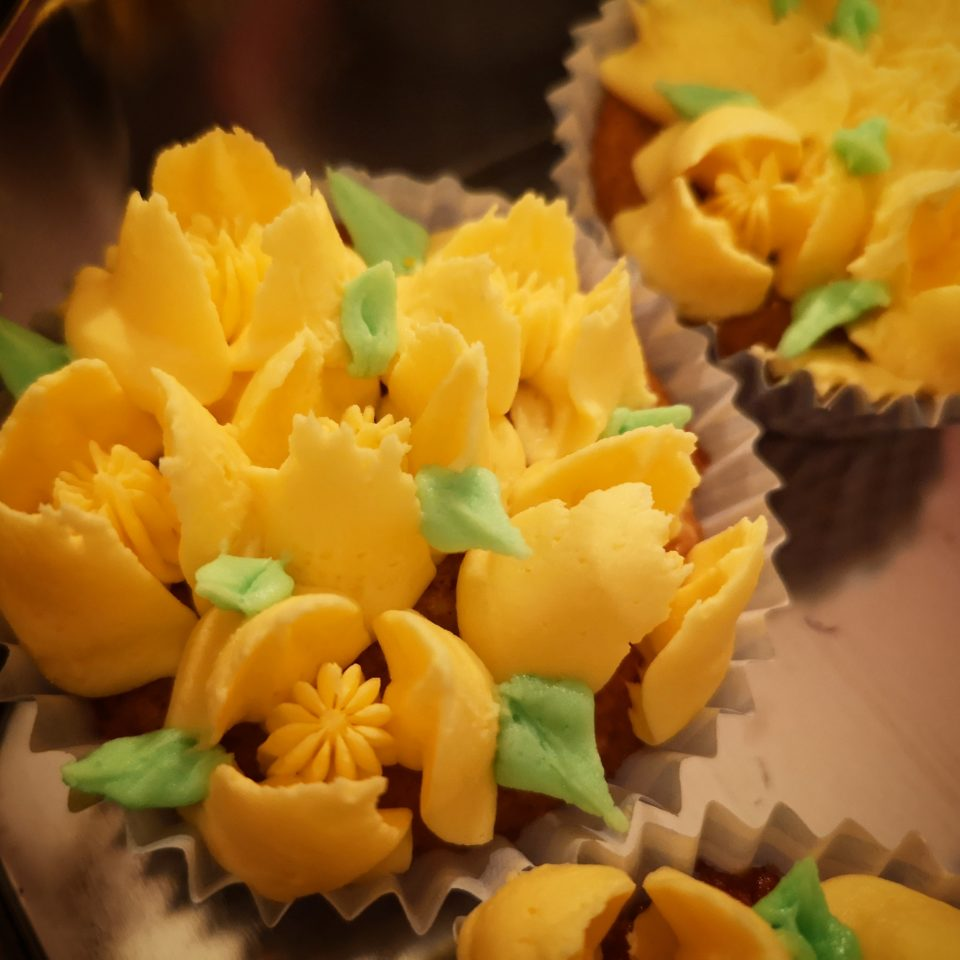 Cupcakes topped with yellow buttercream flowers and green leaves