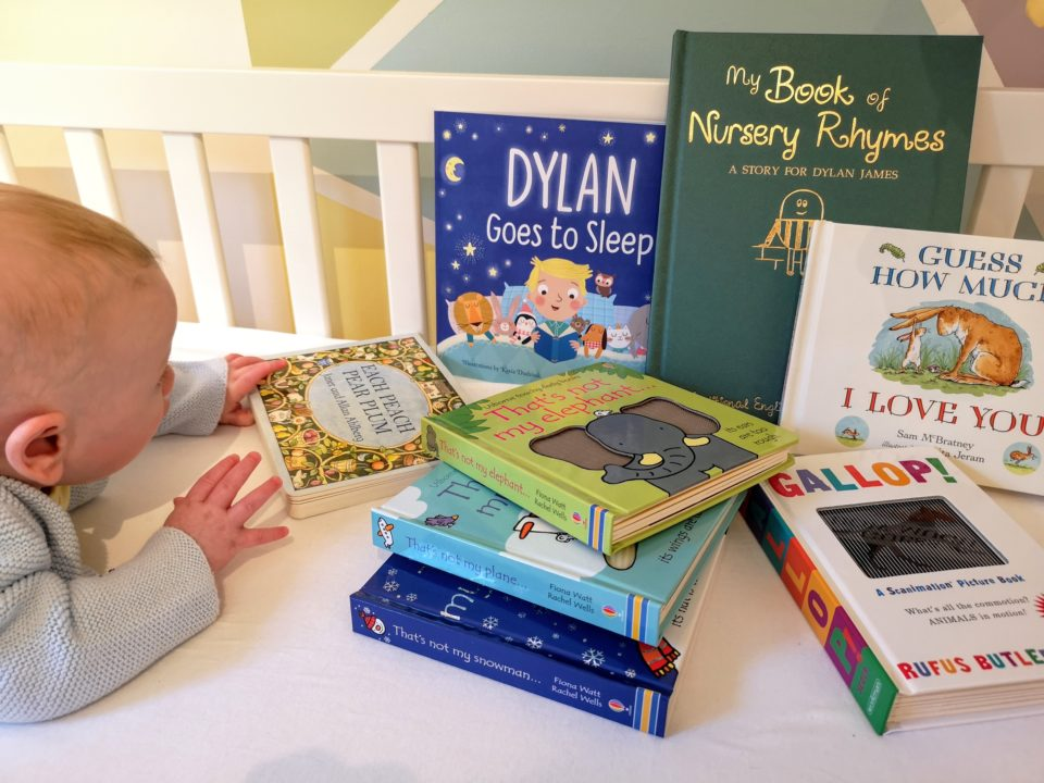 Selection of baby books with baby reaching for one