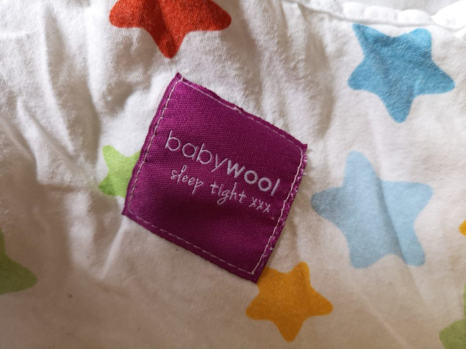 Babywool sleeping bag purple lable on white sleeping bag with colourful star pattern