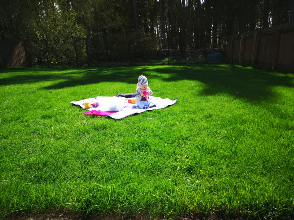 Baby sitting on rug on grass playing with toys