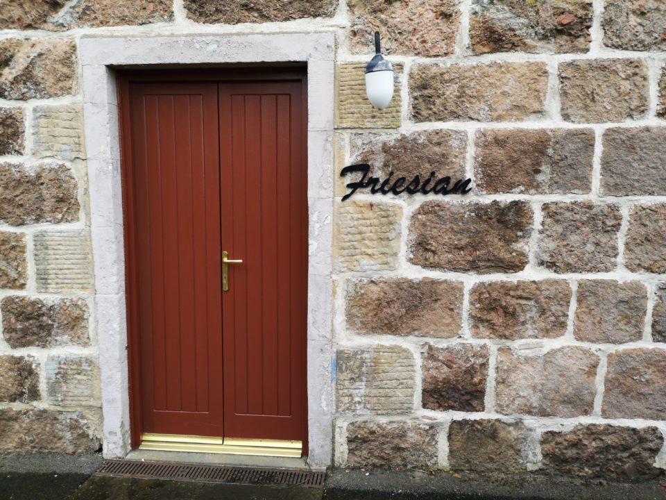 """Wooden double doors set into cottage stone walls with cottage name """"Friesian"""""""