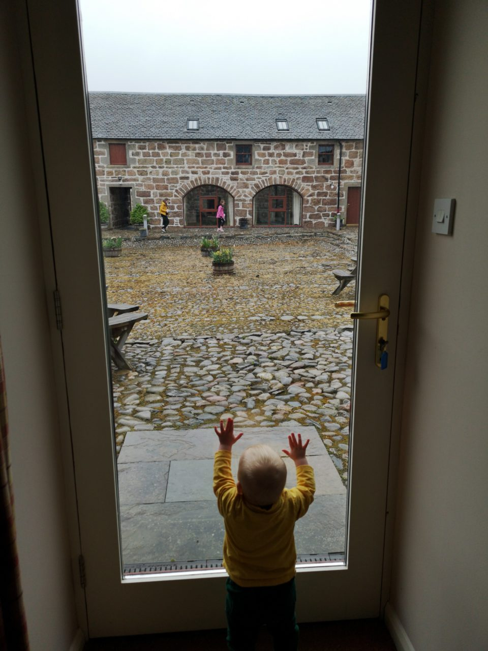 Baby standing at glass door looking into cobbled courtyard