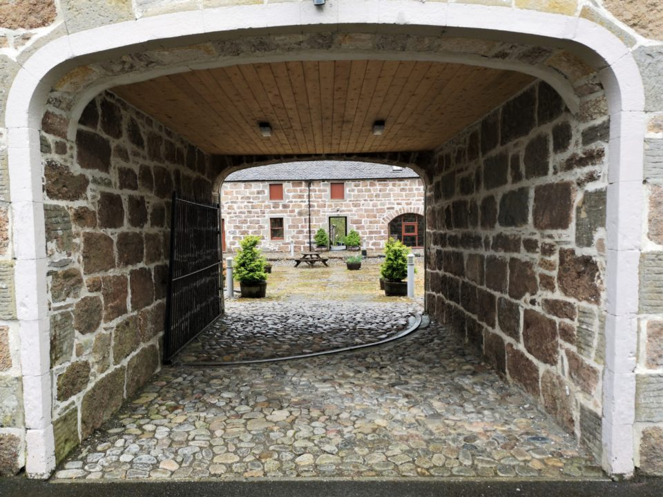 Archway through into cobbled courtyard