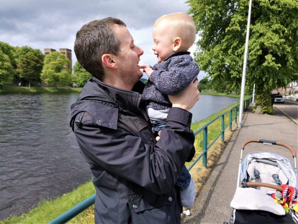 Dad and baby walking next to river