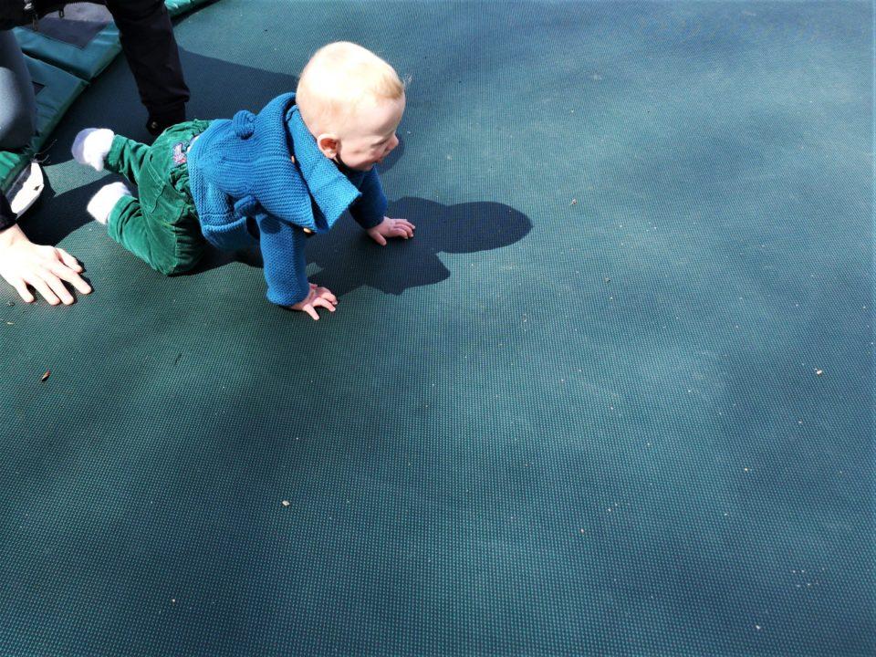 Baby crawling on trampoline
