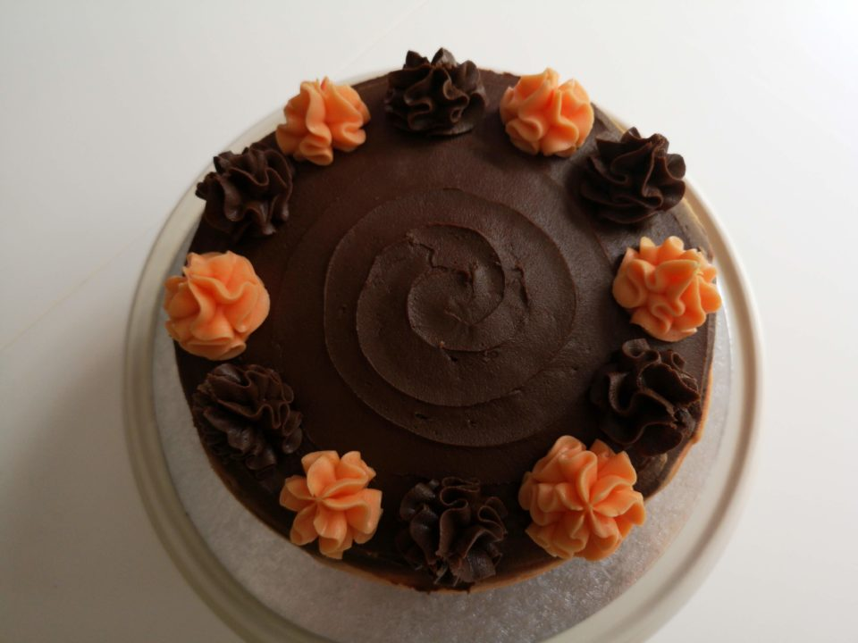 Cake iced using chocolate butter cream with chocolate and orange ruffles around the edge