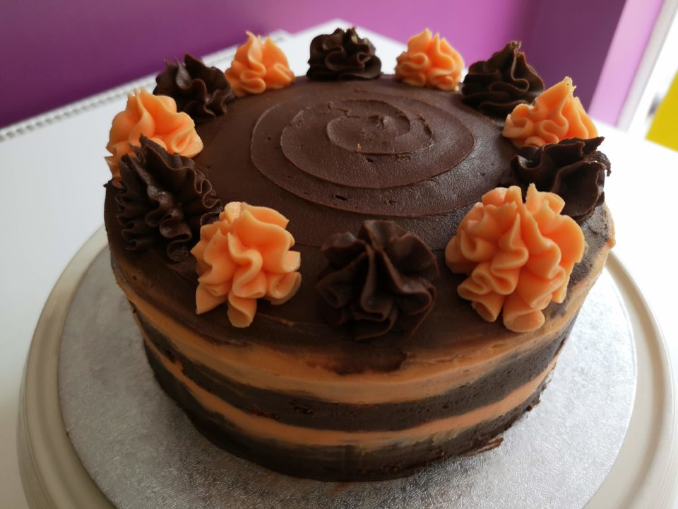 Cake iced using chocolate butter cream with chocolate and orange ruffles around the edge and stripes on the side