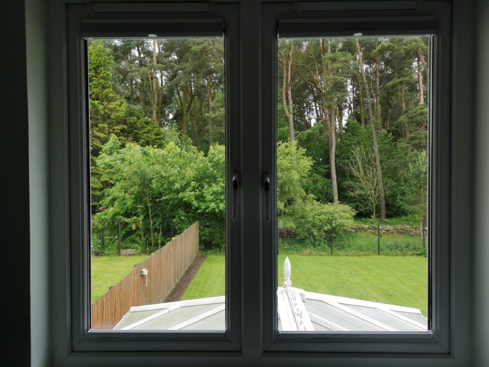 View of a garden through window with open EcoFit blinds fitted