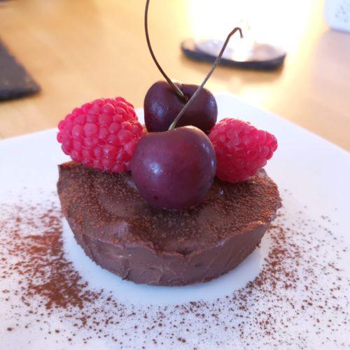 Dark chocolate tart topped with fresh cherries and raspberries