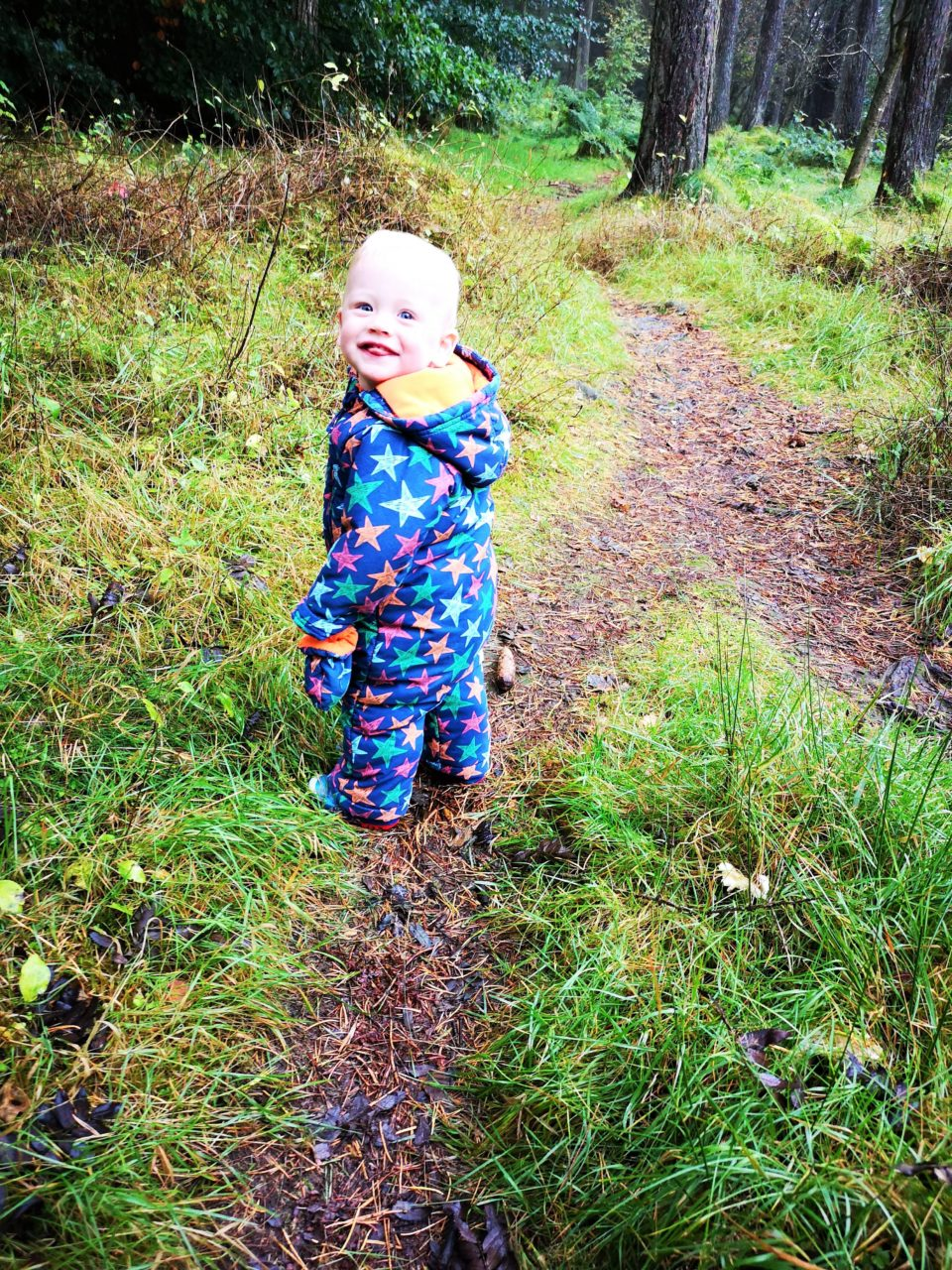 Toddler smiling in the woods