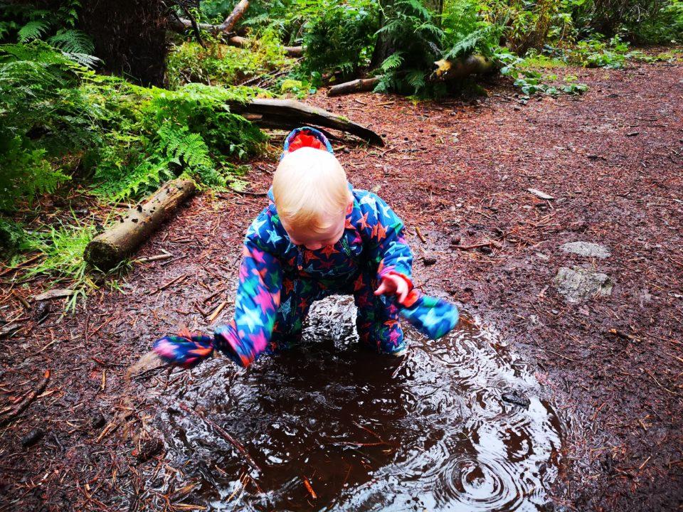 Toddler splashing in a puddle