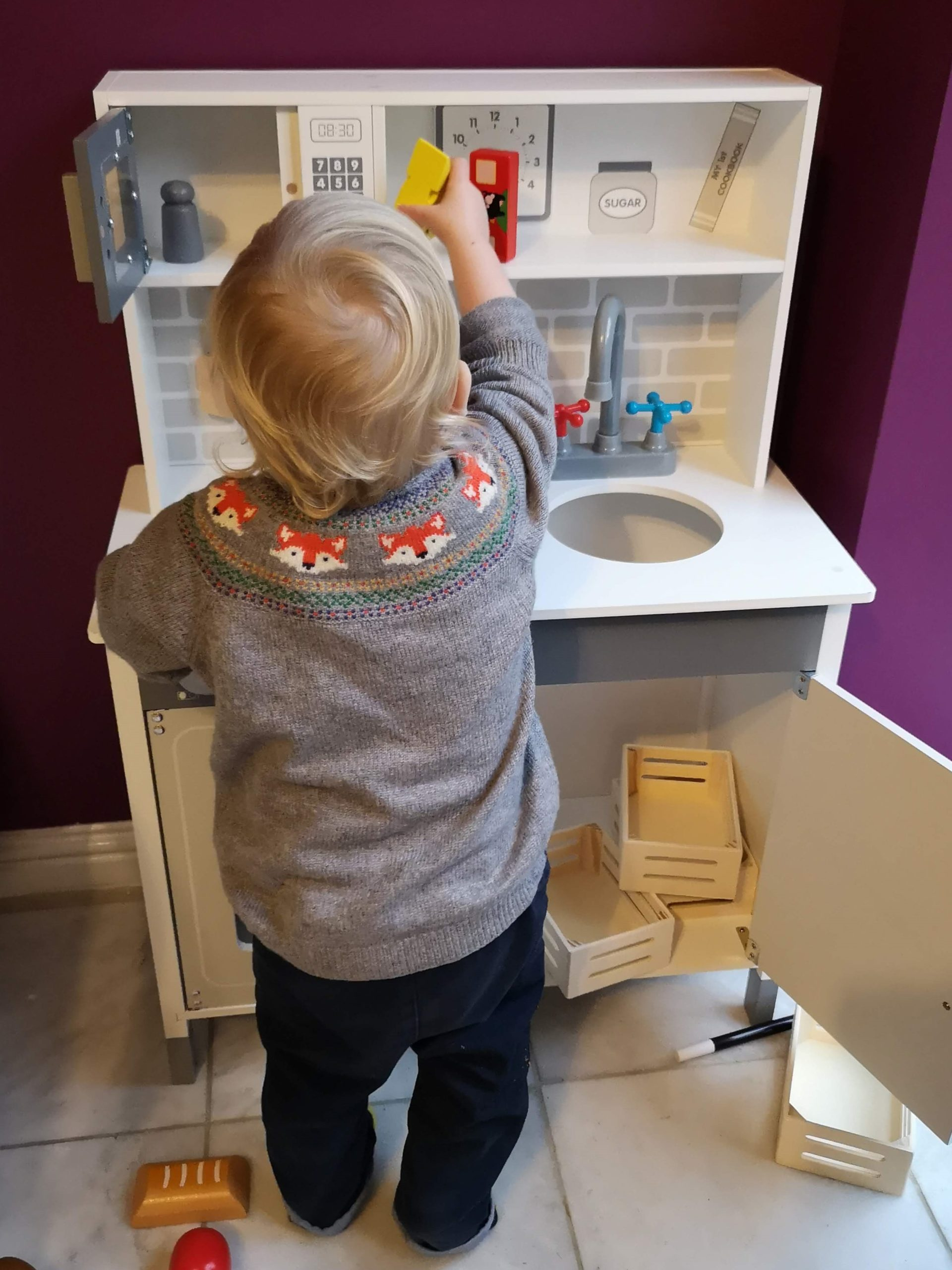 Toddler playing with toy kitchen