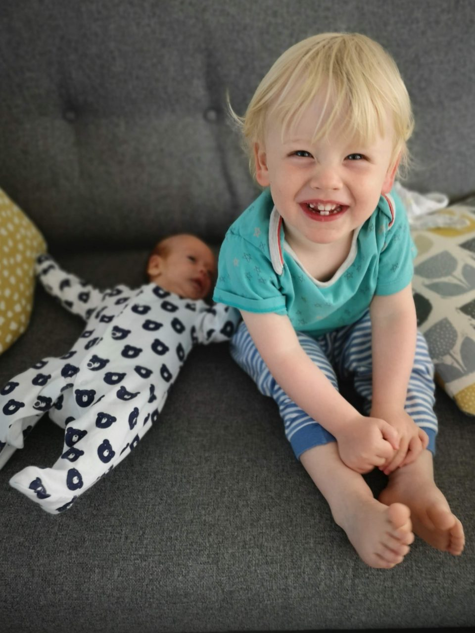 Blond toddler sitting next to newborn baby