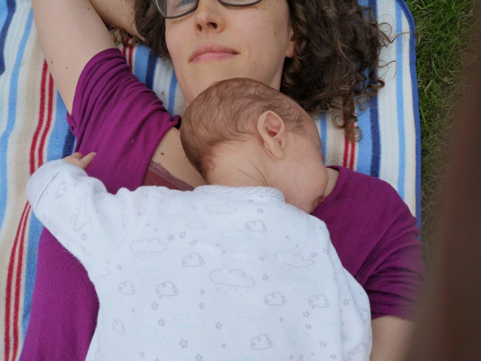 Baby and mum lying on stripy rug