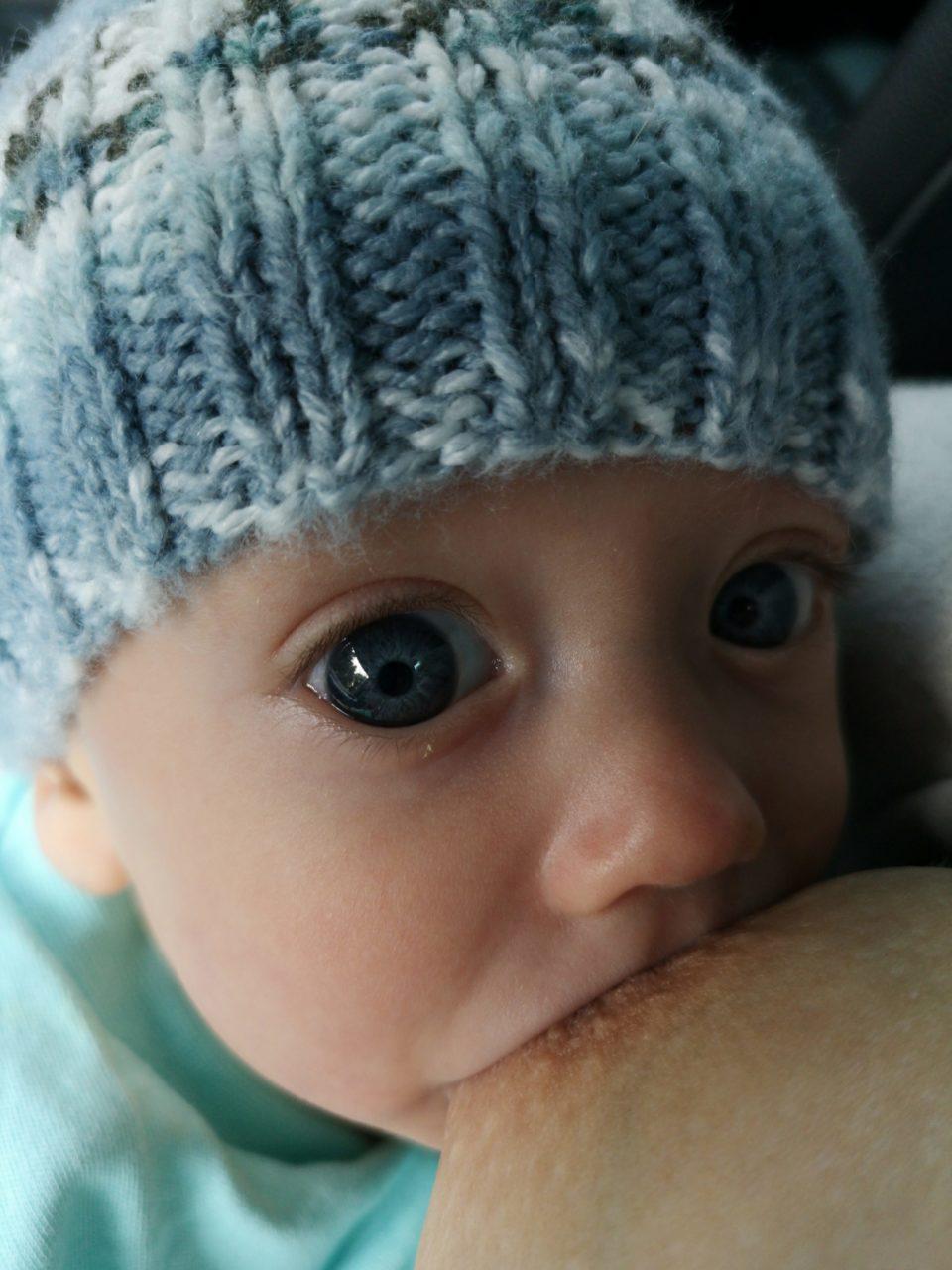 Breastfeeding baby wearing blue at looking up at mum