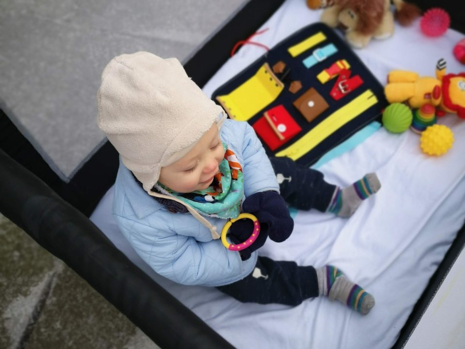 Baby with toys sitting in playpen outside